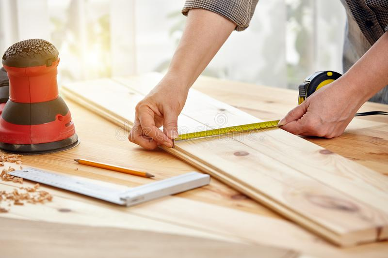 Carpenter works with wood in the workshop. A woman works in a carpentry workshop stock photography