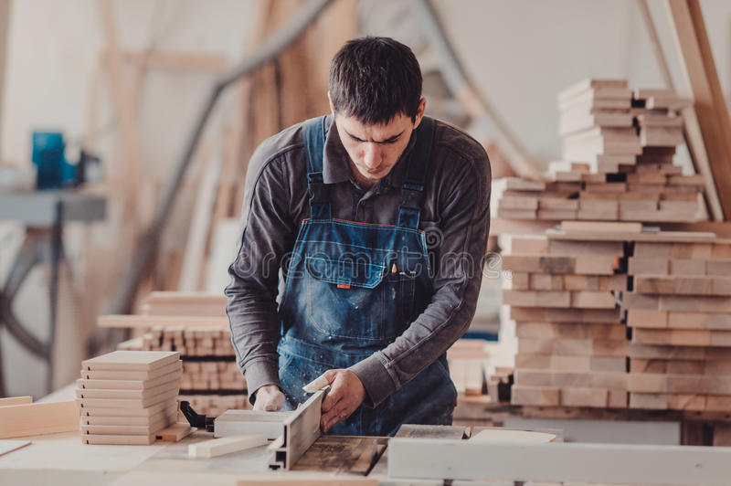 A carpenter works on woodworking the machine tool. Carpenter working on woodworking machines in carpentry shop. royalty free stock images