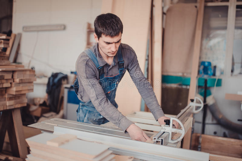 A carpenter works on woodworking the machine tool. Carpenter working on woodworking machines in carpentry shop. stock photography