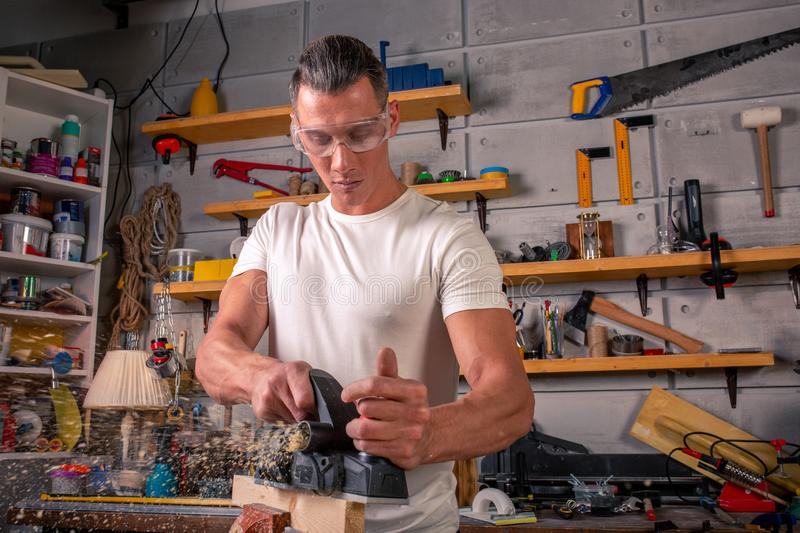 A carpenter works on woodworking the machine tool. Saws furniture details with a circular saw. Process of sawing parts. In parts. Against the background of the stock images