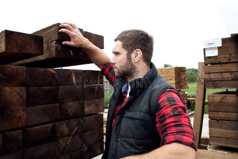 Lumber yard worker, carpenter, choosing, seclecting carrying timber planks royalty free stock photos