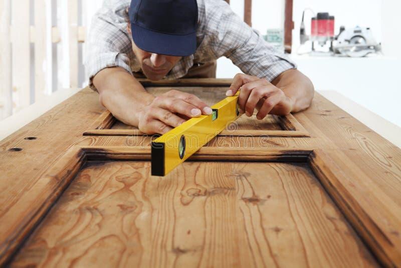 Carpenterr praca drewno mierzy z spirytusowym poziomem fotografia stock