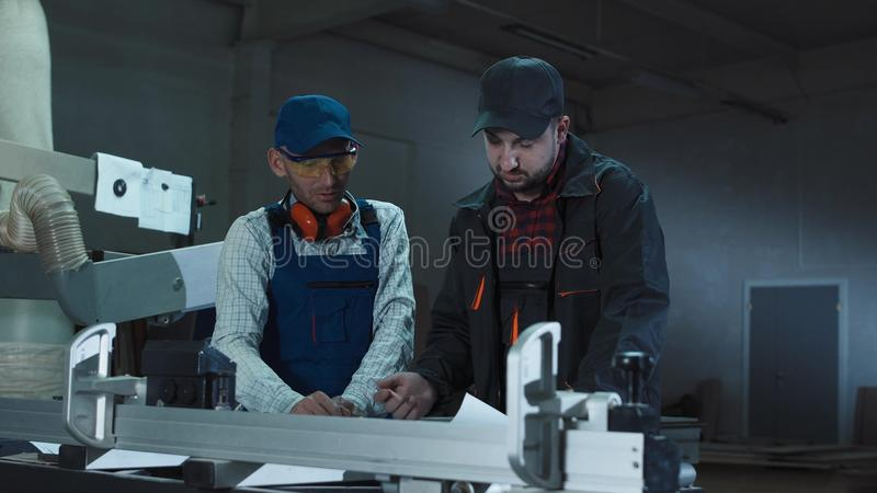 Carpenters with papers in joinery. Carpenters standing in joinery shop and coworking with blueprints stock image