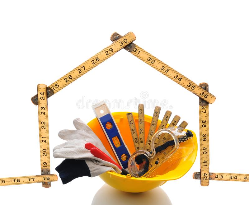 A carpenters ruler in the shape of a house with a hard hat filled with tools and gear royalty free stock photography