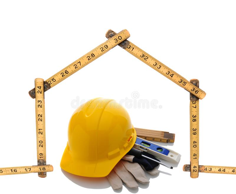A carpenters ruler in the shape of a house with a hard hat and tools stock image