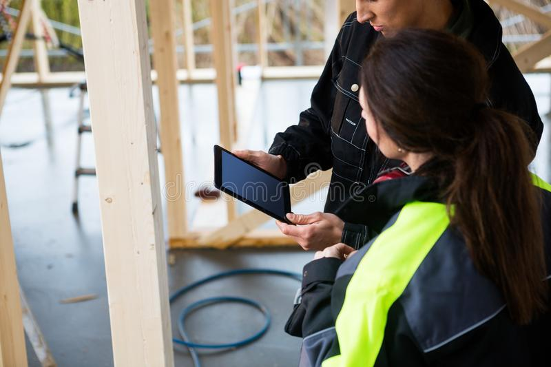 Carpenters Using Digital Tablet In Incomplete Architecture. High angle view of male and female carpenters using digital tablet in incomplete architecture royalty free stock photos
