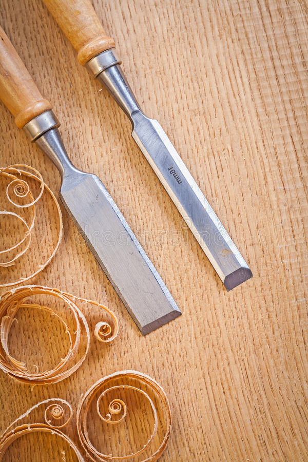 Carpentery chisels on wooden board with wooden shavings royalty free stock images