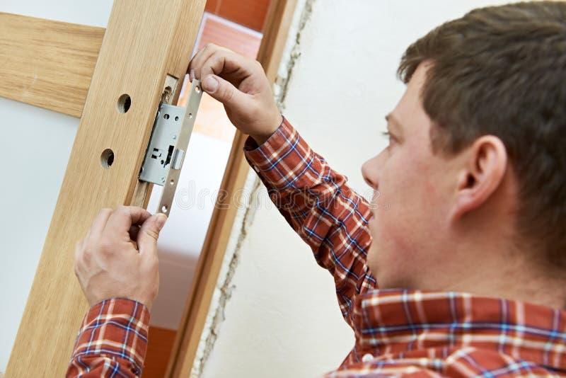 Carpentiere all'installazione della serratura di porta fotografia stock libera da diritti