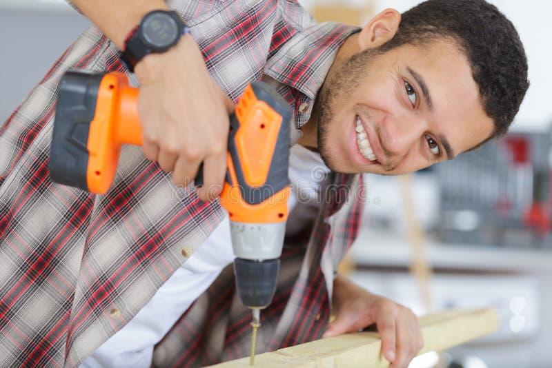 Carpentiere bello che sorride mentre lavorando con il legno immagini stock libere da diritti