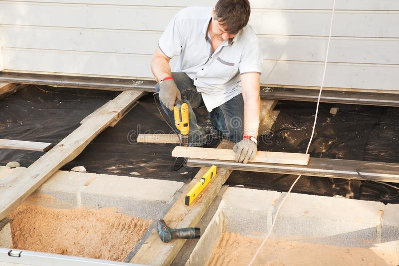 Carpentiere bello del giovane che installa un terrazzo all'aperto del pavimento di legno nel cantiere della nuova casa immagine stock libera da diritti