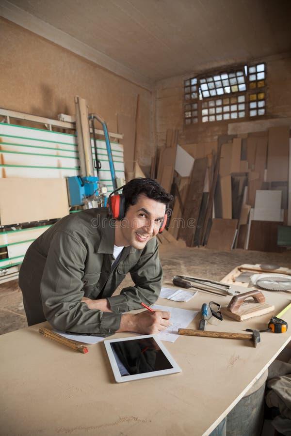 Carpentiere bello Working On Blueprint dentro fotografia stock libera da diritti