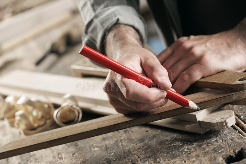 Carpentiere che contrassegna una plancia di legno fotografie stock