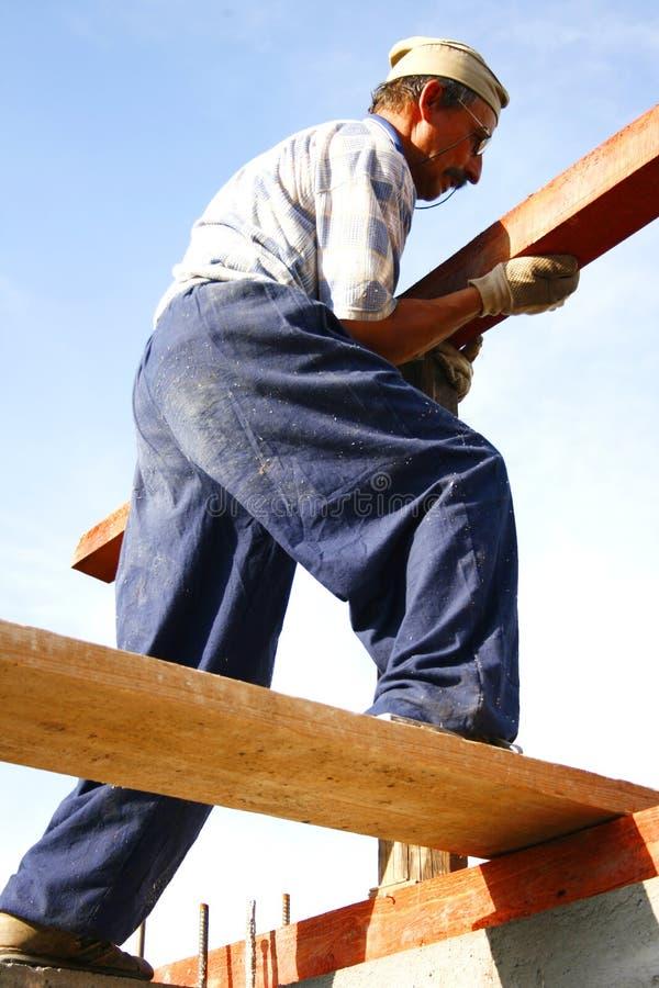 Carpentiere che fa grande sforzo immagini stock
