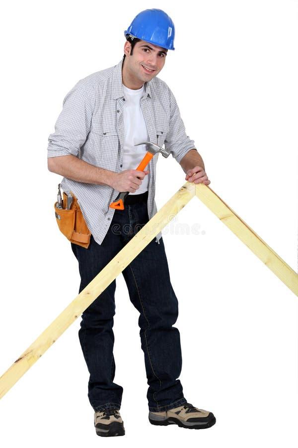 Carpentiere che inchioda un blocco per grafici fotografia stock