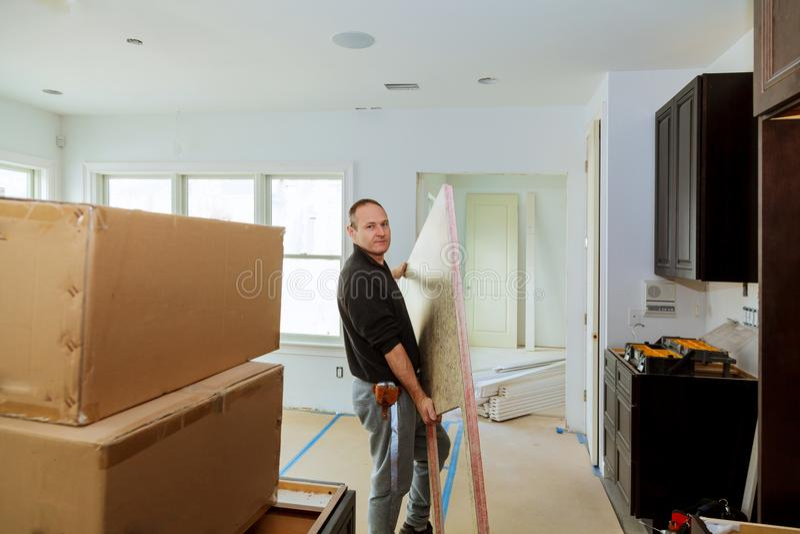 Carpentiere che installa i gabinetti e ripiano nella cucina fotografia stock