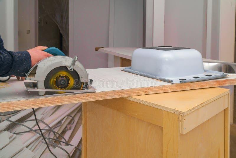 Carpentiere che installa un foro tagliato di ritocco in un ripiano laminato fotografia stock libera da diritti