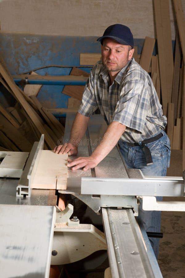 Carpentiere che lavora alle macchine di falegnameria fotografie stock libere da diritti