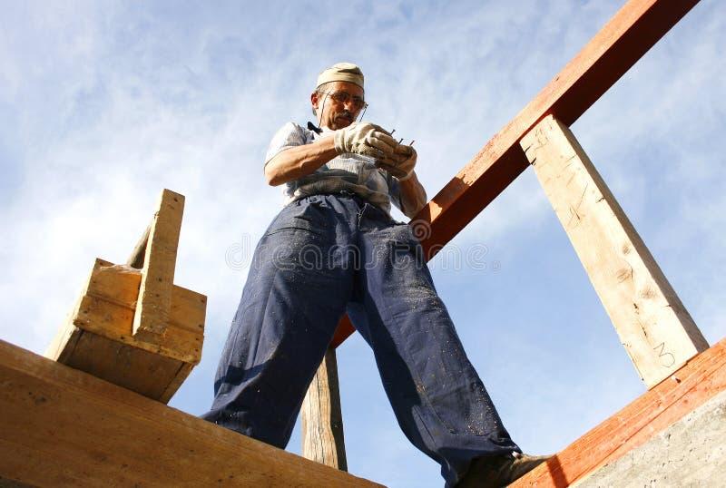 Carpentiere che lavora con i chiodi e una casella di legno fotografie stock