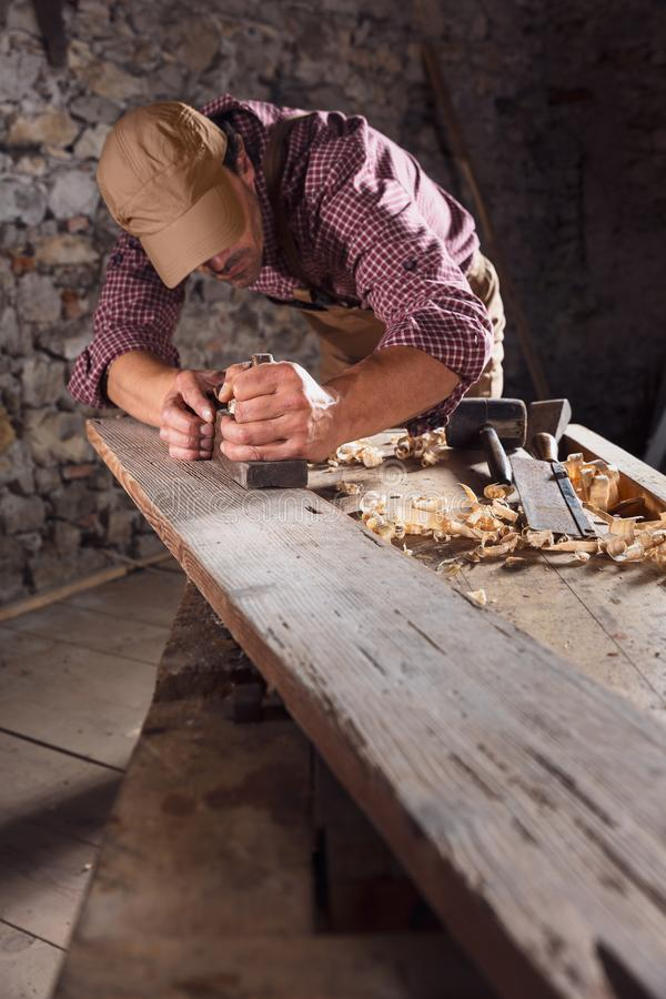 Carpentiere che liscia fuori fascio di legno lungo con lo strumento immagini stock libere da diritti