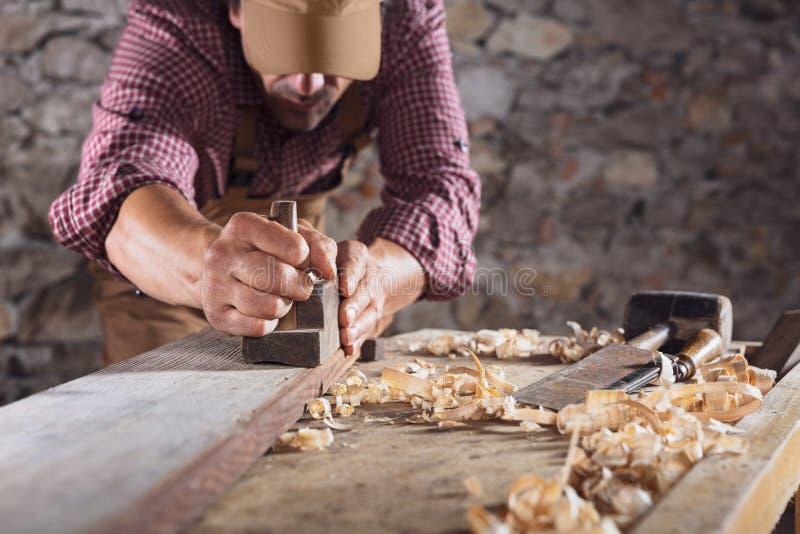 Carpentiere che liscia fuori fascio di legno lungo con lo strumento immagine stock