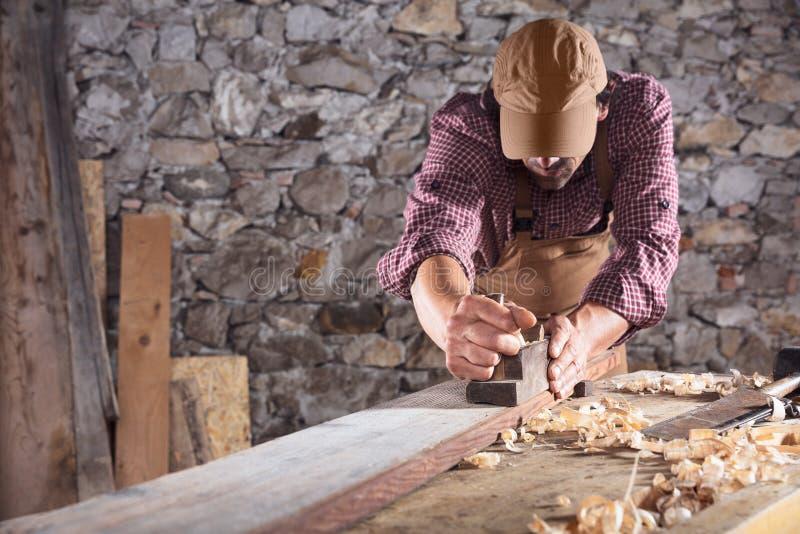 Carpentiere che liscia fuori fascio di legno lungo con lo strumento fotografia stock libera da diritti