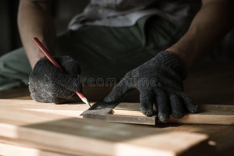 carpentiere che misura e che scrive sul legno con il backgro dello spazio della copia immagini stock