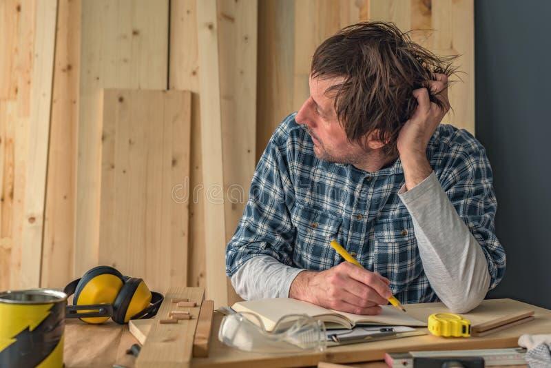 Carpentiere che pensa nell'interno dell'officina della lavorazione del legno di piccola impresa immagini stock libere da diritti
