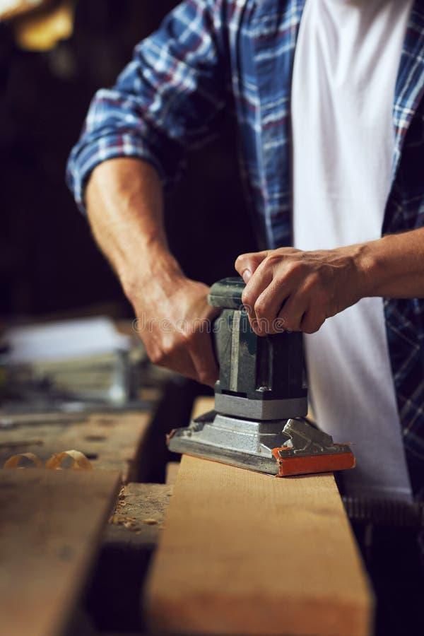 Carpentiere che per mezzo della sabbiatrice elettrica sul bordo di legno immagini stock