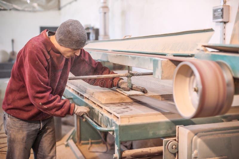 Carpentiere che per mezzo della smerigliatrice a nastro immagine stock libera da diritti