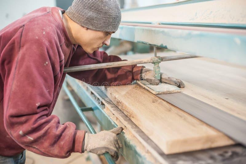 Carpentiere che per mezzo della smerigliatrice a nastro immagini stock libere da diritti