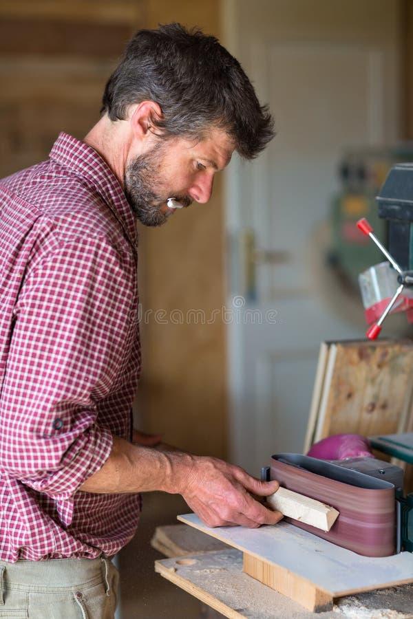 Carpentiere che per mezzo dello strumento della sabbiatrice elettrica immagini stock