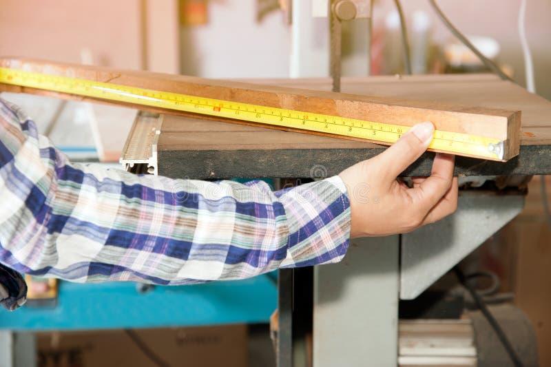 Carpentiere che per mezzo di un nastro di misurazione fotografie stock libere da diritti