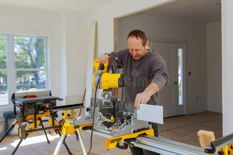 Carpentiere che per mezzo di una sega circolare per tagliare bordo di legno immagini stock