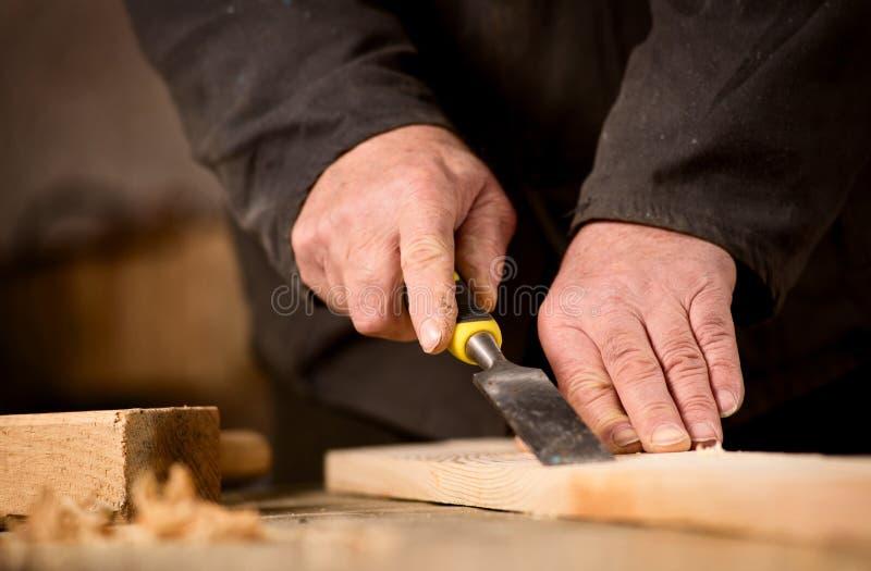 Carpentiere che per mezzo di uno scalpello su una plancia di legno immagini stock libere da diritti