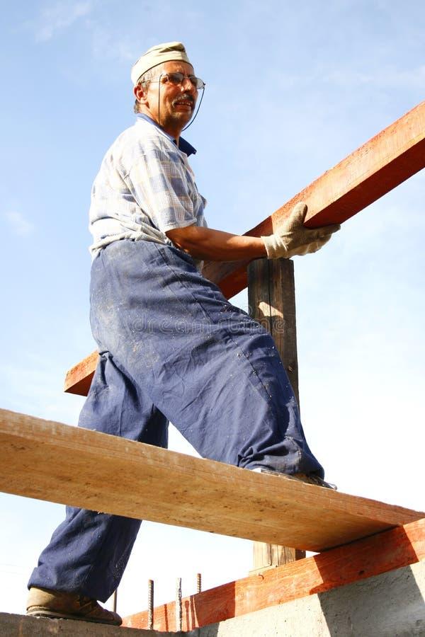 Carpentiere che ripara un legno lungo fotografia stock