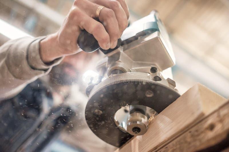 Carpentiere che usando falegnameria elettrica che dirige una plancia di legno immagini stock libere da diritti