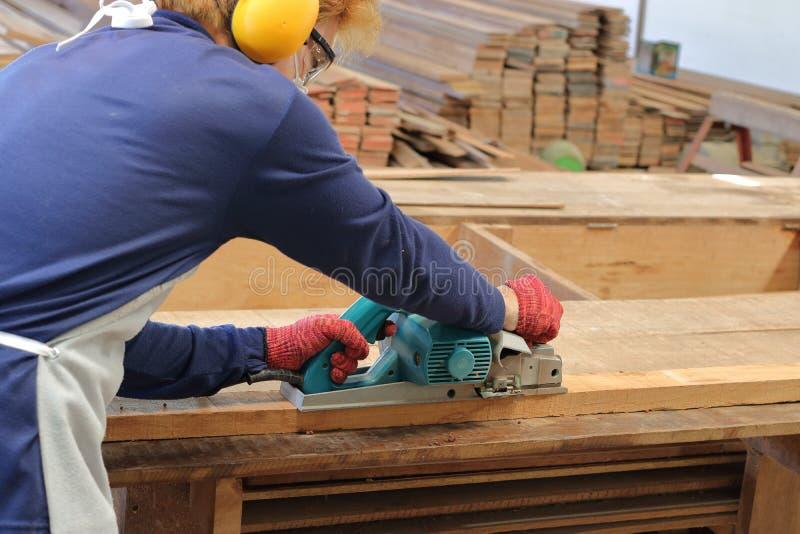 Carpentiere che utilizza piallatrice elettrica con la plancia di legno nell'officina di carpenteria immagini stock