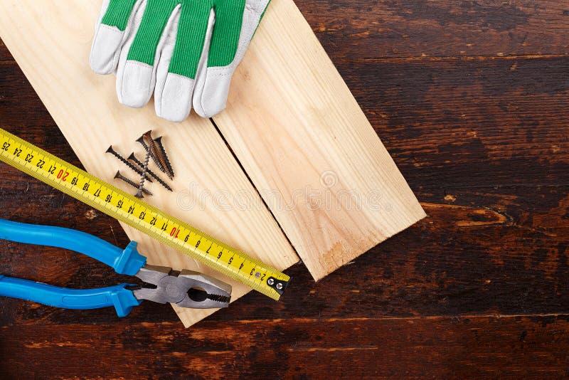 Carpentiere degli attrezzi su un fondo di legno fotografia stock libera da diritti