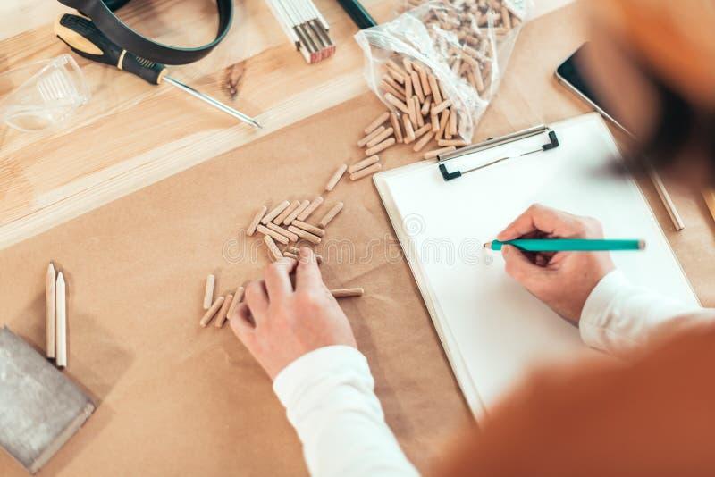 Carpentiere femminile che lavora con i perni di legno fotografie stock