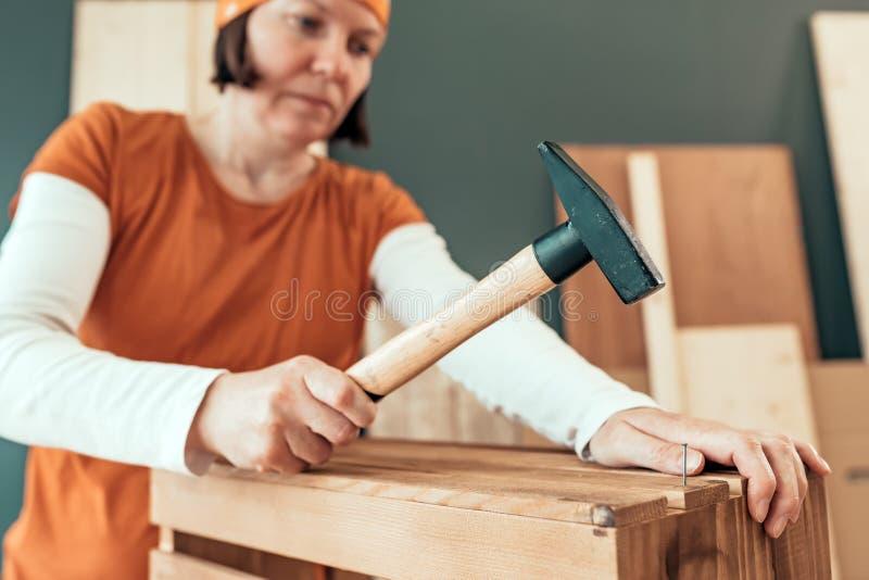 Carpentiere femminile che martella chiodo nella cassa di legno fotografia stock libera da diritti