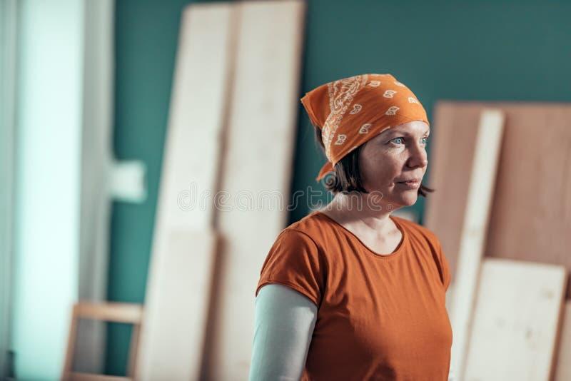 Carpentiere femminile con il bandanna che posa nell'officina della lavorazione del legno immagine stock