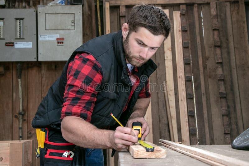 Carpentiere, lavoro del legno del lavoratore che misura, perforante e facente il prodotto del legname immagini stock libere da diritti
