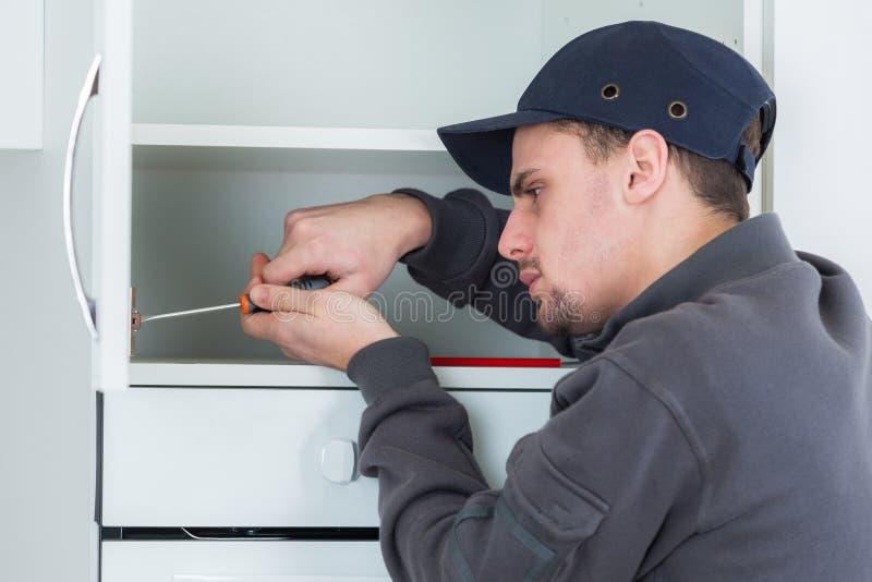 Carpentiere maschio che installa gabinetto nella cucina dei clienti immagini stock