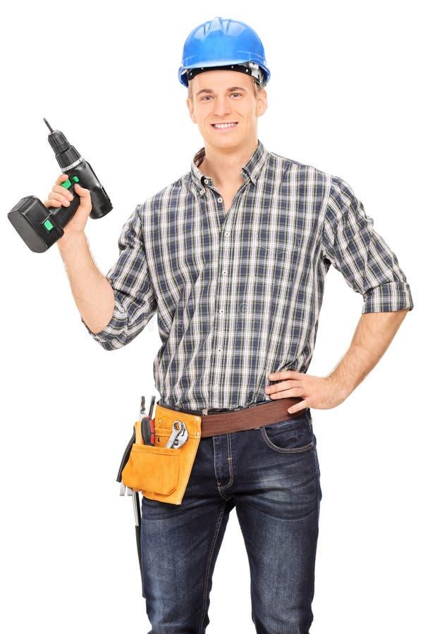 Carpentiere maschio con il casco che tiene un trapano fotografie stock