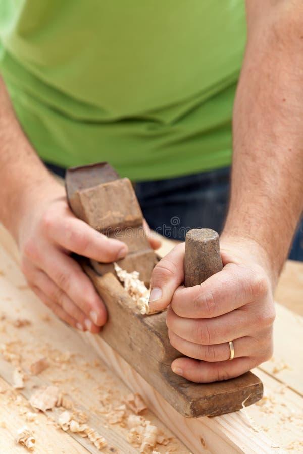 Carpentiere o falegname che lavora con l'aereo immagine stock libera da diritti