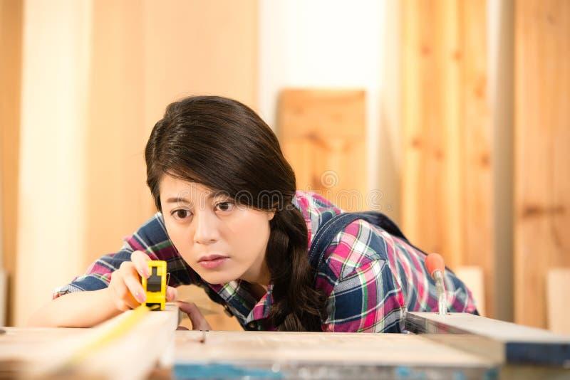 Carpentiere occupato che per mezzo di un nastro di misurazione fotografia stock libera da diritti