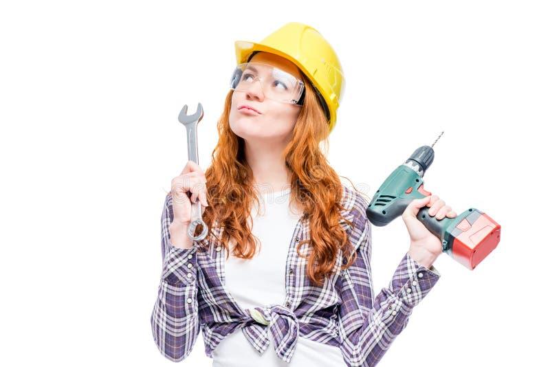 carpentiere pensieroso della donna in casco su fondo bianco fotografia stock