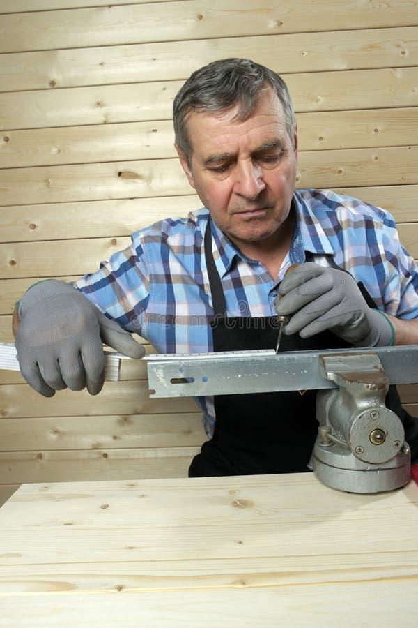 Carpentiere senior che lavora nella sua officina fotografia stock libera da diritti