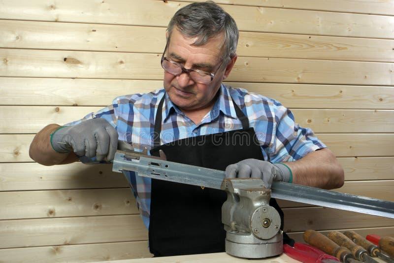 Carpentiere senior che lavora nella sua officina immagine stock libera da diritti