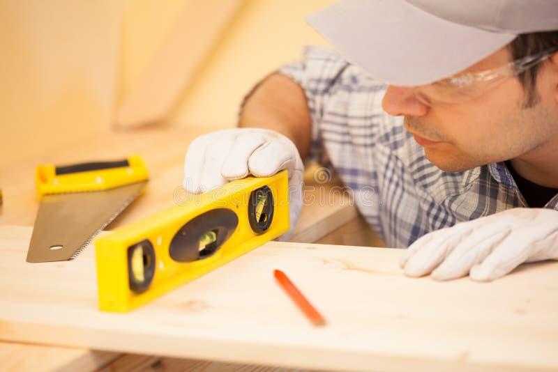 Carpentiere sul lavoro facendo uso di una livella a bolla fotografia stock